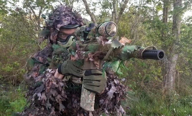 Evan Grantham in leafy suit holding EMF100 in rifle wrap